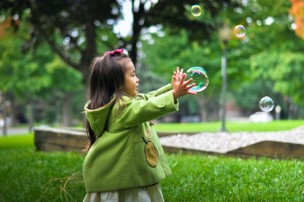 Small girl playing in park with bubbles