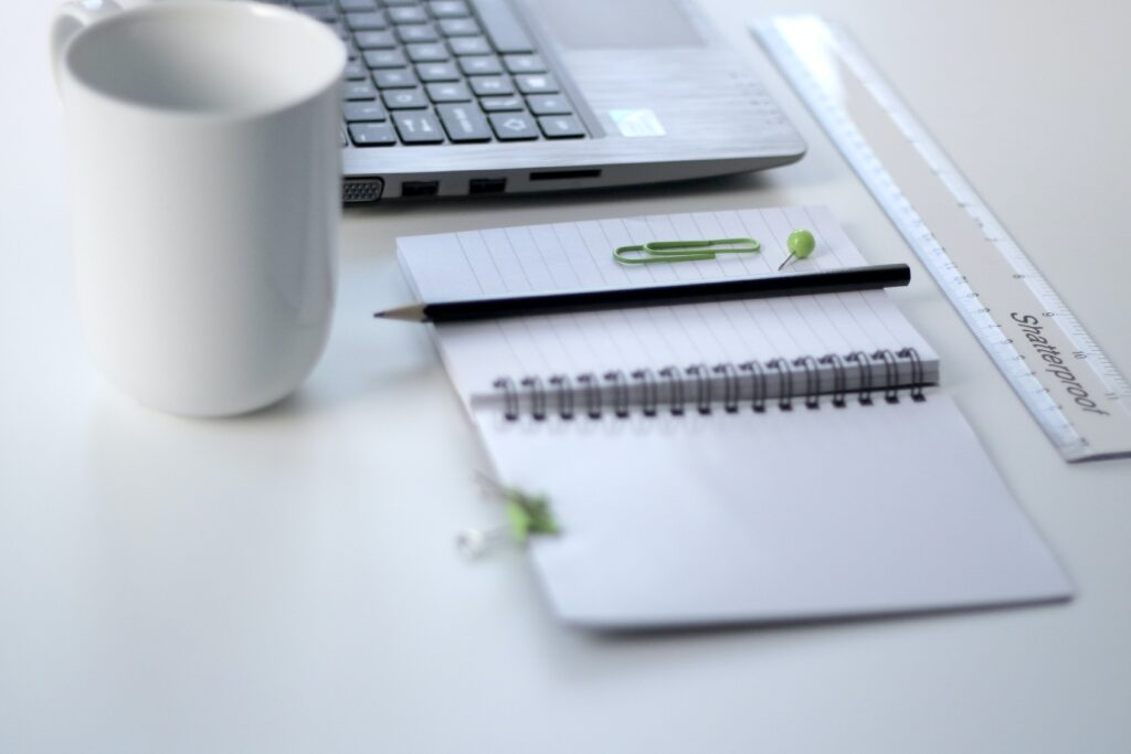 Photo of desk with notebook, stationary, a cup and a laptop