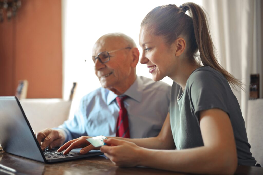 Young woman sitting with older man at laptop