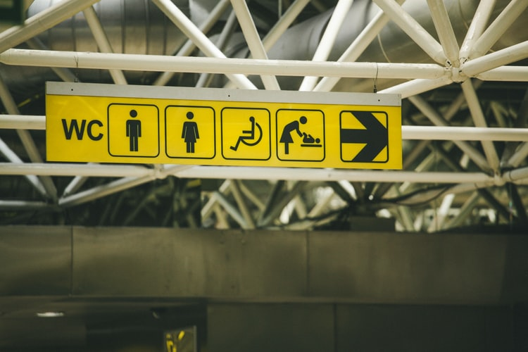 Yellow sign showing symbols for toilets, including disabled toilet
