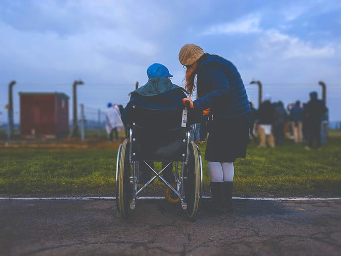 Standing woman leaning to talk to person in wheelchair