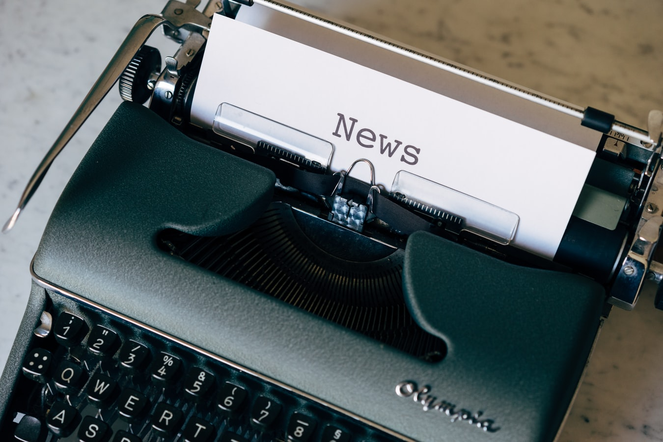 Typewriter with piece of paper where it has been types the word News