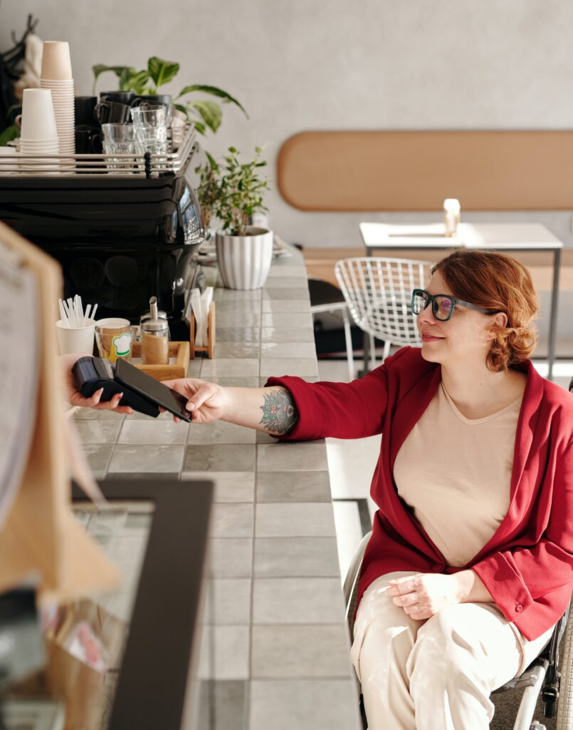 Woman paying for drink in cafe