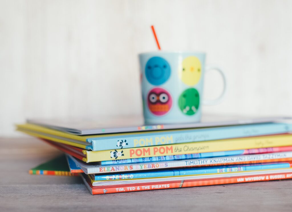 A pile of childrens books and a children's mug with a straw