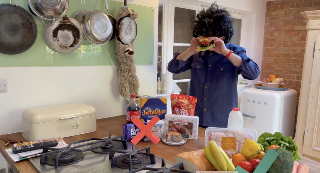 Phil, in disguises wearing a big black bushy wig, is caught biting into a big burger. In front of him is two groups of food. In front of one group, consisting of coca-cola, Jaffa Cakes, crisps etc is a big red cross, in front of the other group of fruit and veg, is a green tick