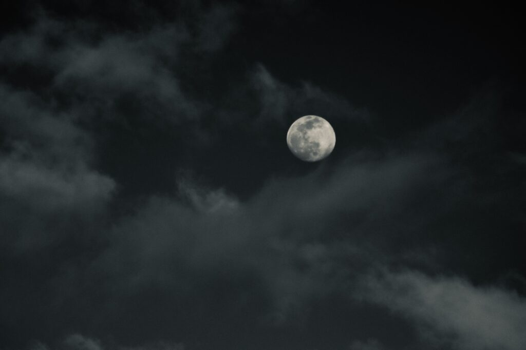 Photo of the night sky, showing the moon and clouds