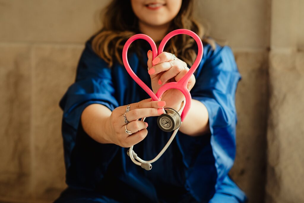 A young woman in medical scrubs holds a stethoscope, it's cable shaped into a heart
