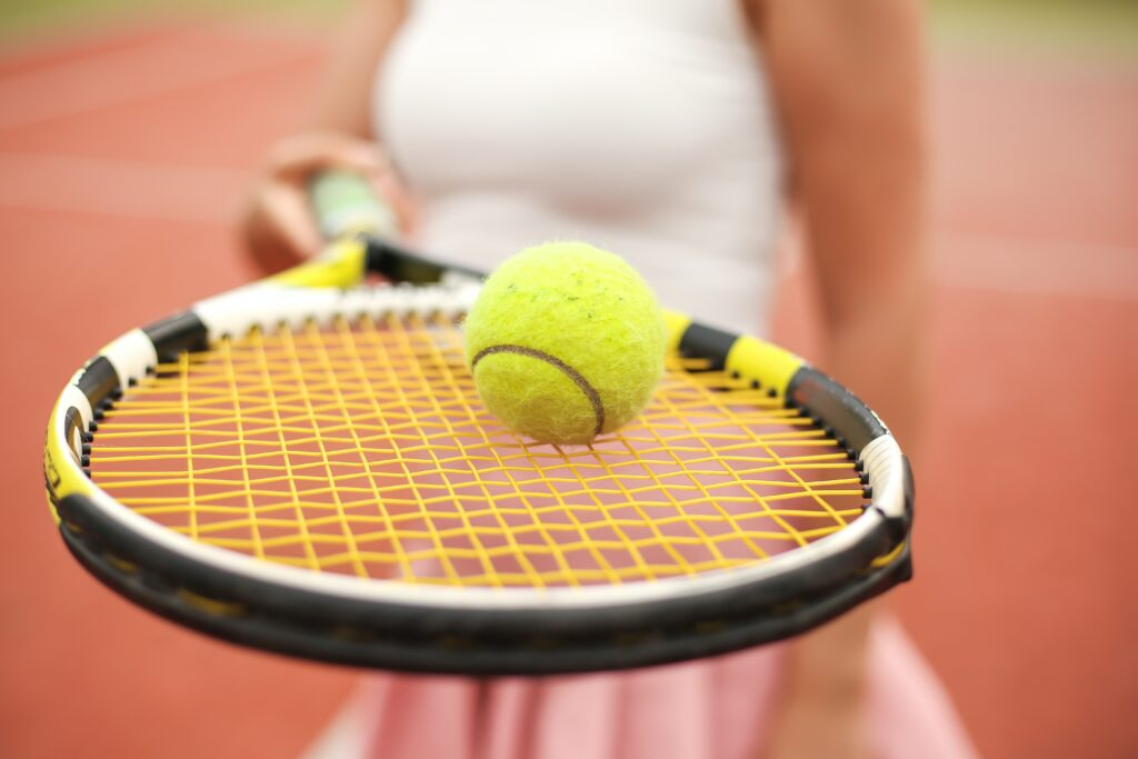 Close up photo of a woman holding out a tennis racket with a ball balanced on it