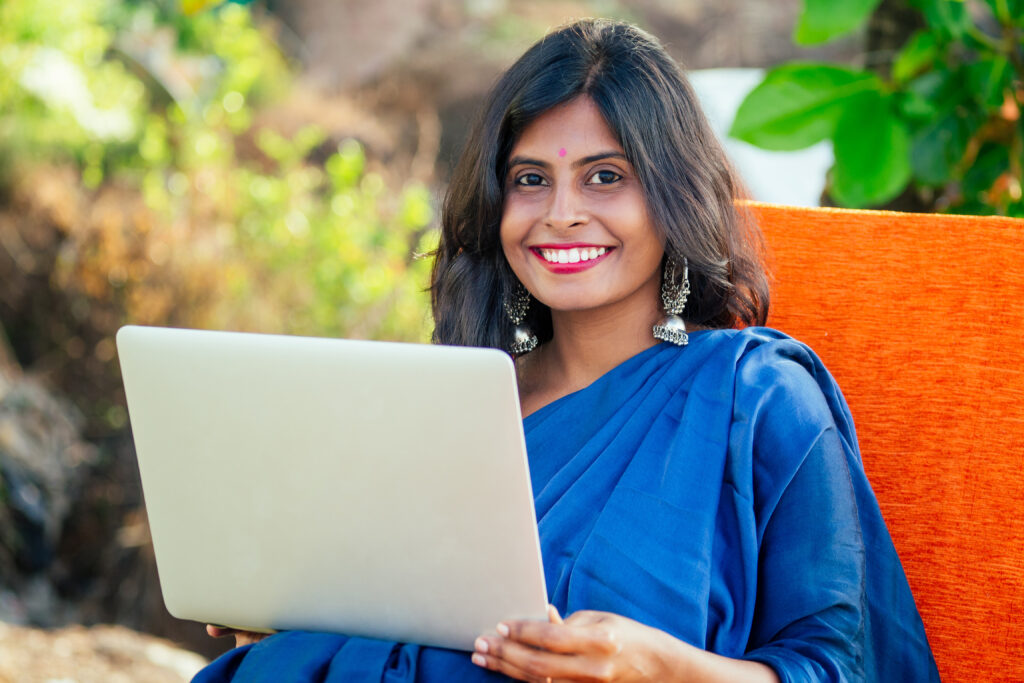 A young woman in traditional Indian dress sits smiling at a laptop