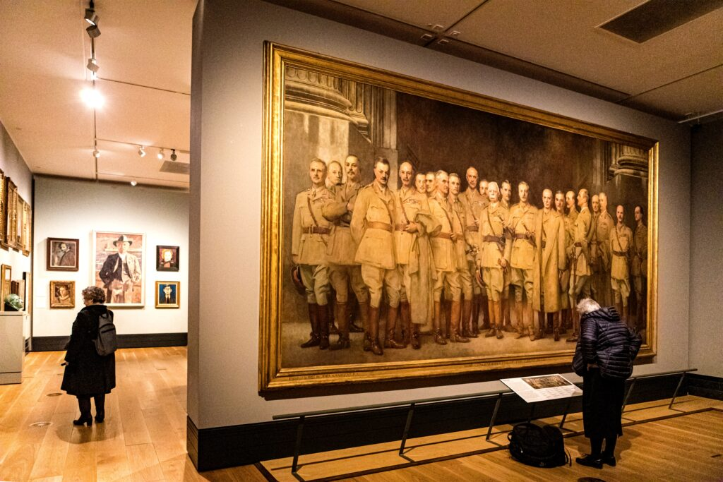 A museum gallery, showing large pictures of men in uniform on the wall. Two people are looking at the paintings