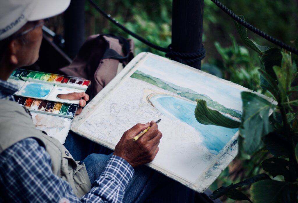 An older artist is painting outside